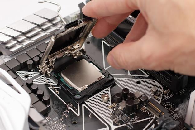 Main mettant un processeur sur une carte mère d'un ordinateur.
