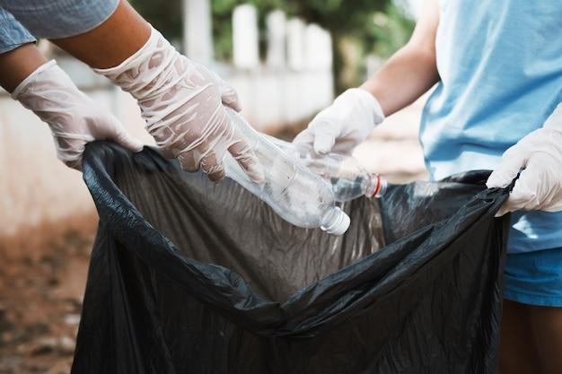 Main mettre une bouteille en plastique vide dans un sac poubelle noir