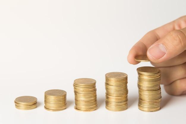 Main mettre des pièces de monnaie sur la pile, économiser de l'argent et le concept d'entreprise.