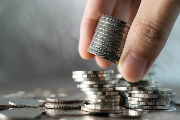 Main mettre des pièces de monnaie à la pile de pièces, concept d'investissement et d'épargne.