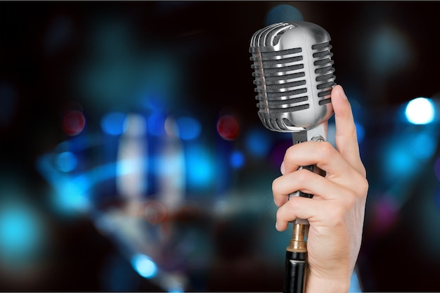 Main avec microphone sur fond flou