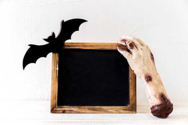 Main de monstre et chauve-souris près du tableau noir