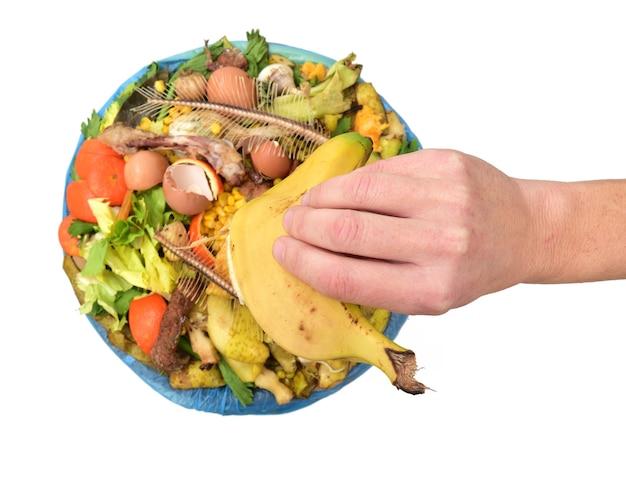 Main montrant une banane pour le recyclage organique sur fond blanc