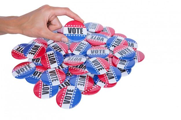 Main montrant l'insigne de vote derrière la pile d'insigne