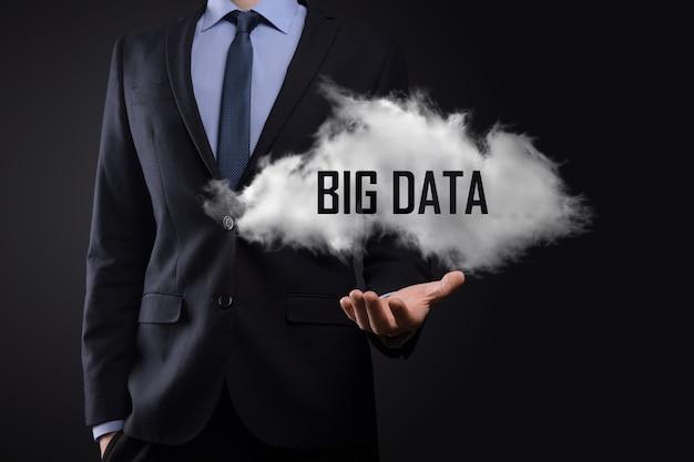 Main montrant un nuage avec les mots big data sur fond sombre.