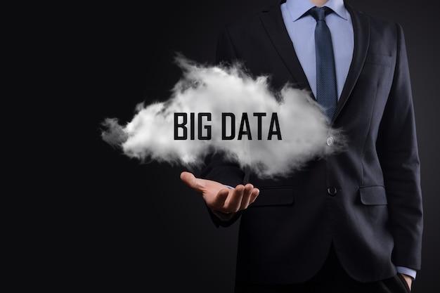 Main montrant un nuage avec les mots big data sur une surface sombre