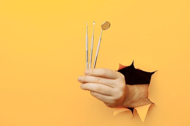 Main montrant des outils de dentiste hors d'un trou déchiré dans le concept de soins de santé de mur jaune