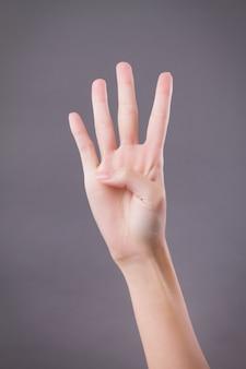 Main montrant, pointant vers le haut quatre doigts, numéro quatre geste de la main