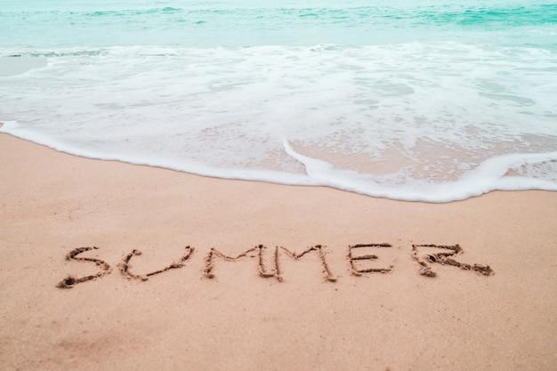 Main de mot d'été dessiné sur la plage d'été de sable.