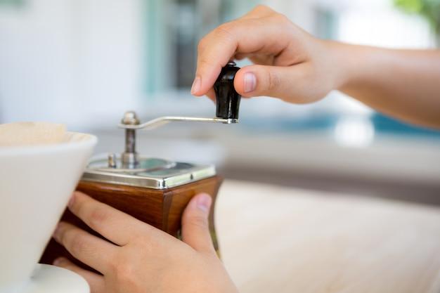 Main moudre le café avec un broyeur et une tasse à côté
