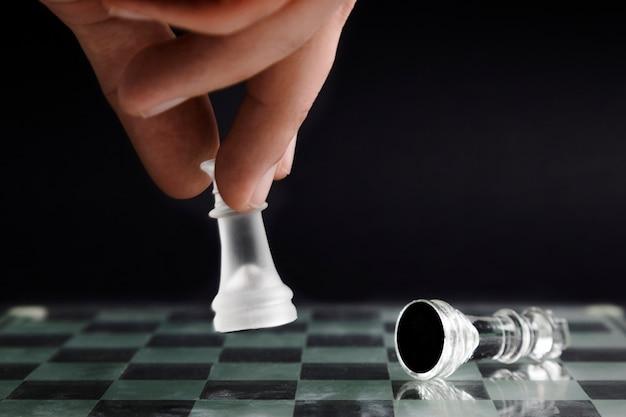 Main en mouvement des pièces d'échecs transparentes