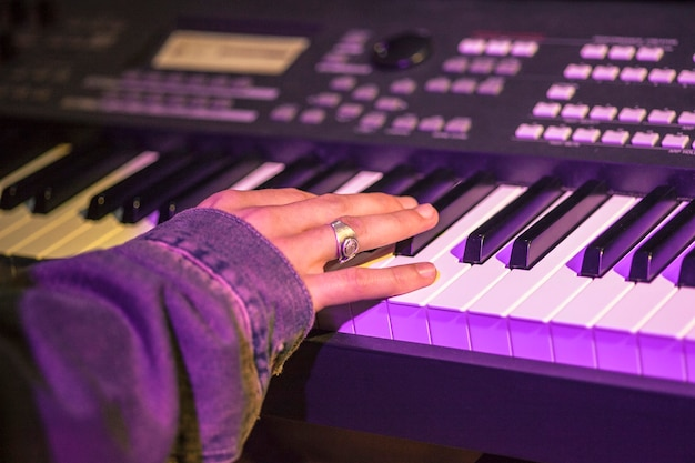 Main d'un musicien au piano éclairé par des projecteurs colorés