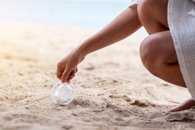 Une main nettoyant et ramassant une poubelle en verre en plastique sur la plage