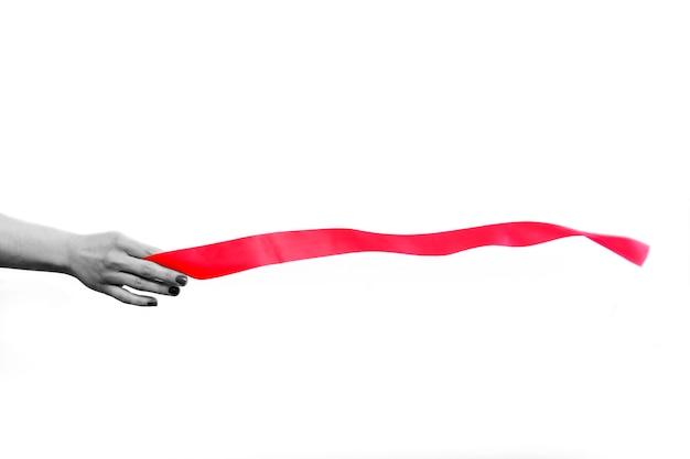 Main noire et blanche tenant le ruban rouge