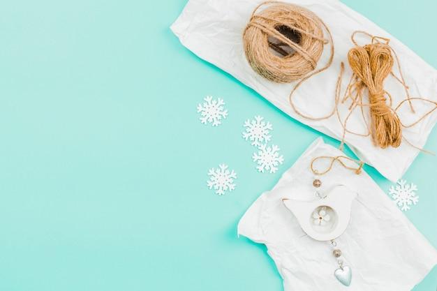 Main oiseau en bois suspendu sur papier avec fil et flocon de neige sur fond turquoise