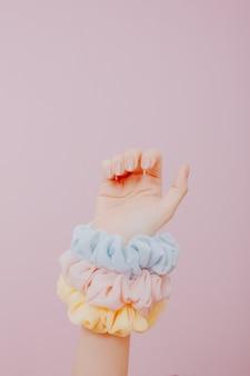Main avec des ongles peints et des chouchous sur le bras