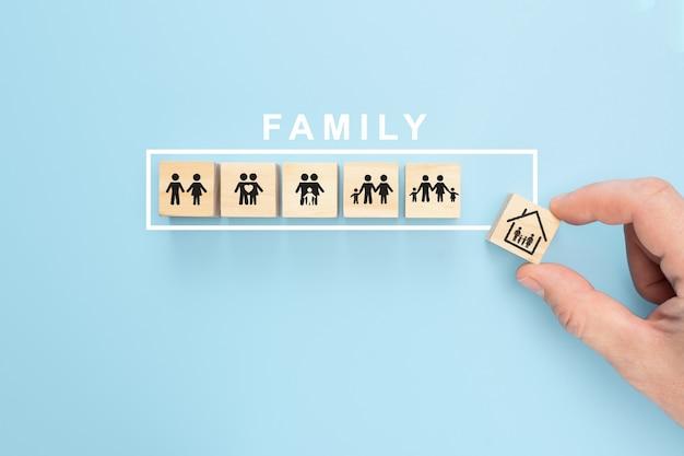Main organisant le cube de bois avec le symbole de la famille sur fond bleu pastel