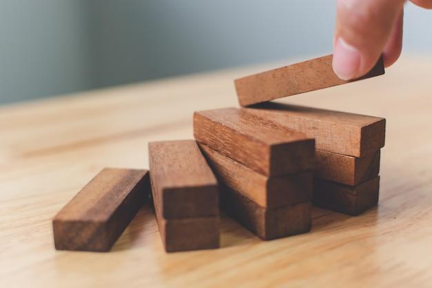 Main organisant l'empilement de blocs de bois comme marche d'escalier. concept de parcours en échelle pour le processus de réussite de croissance