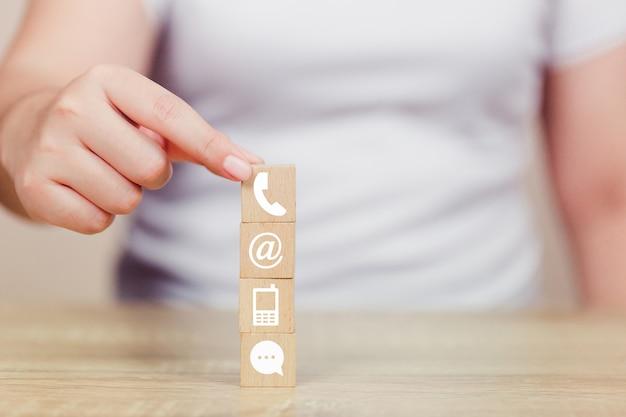 Main organisant l'empilement de blocs de bois avec téléphone, courrier, adresse et téléphone portable d'icône