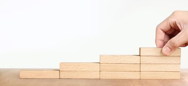 Main organiser un bloc de bois comme escalier en escalier, processus de réussite de croissance de concept d'entreprise