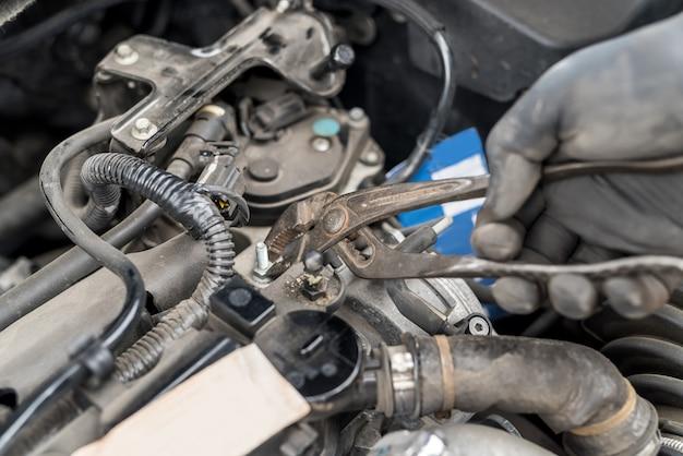 Main avec outil, écrou de fixation dans le moteur de la voiture, gros plan