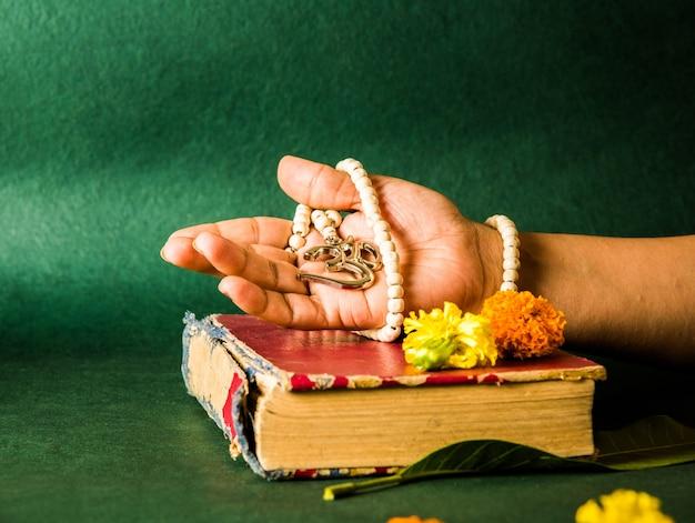 Main ouverte montrant le médaillon d'aum avec des perles, un livre hindou rouge à la surface avec des fleurs