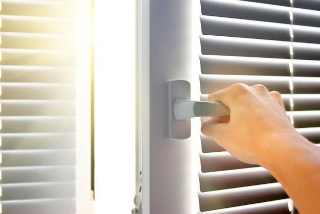 Main ouvrant une fenêtre pour laisser entrer le soleil