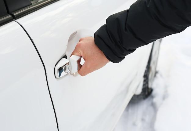 Une main ouvrant une porte avant de voiture