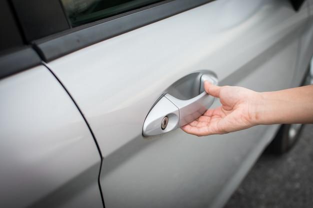 La main ouvre la porte de la voiture.