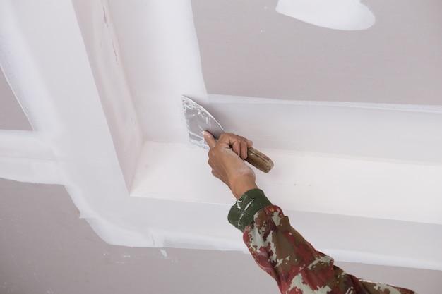 Main de l'ouvrier utilisant des joints de plafond en plâtre de gypse