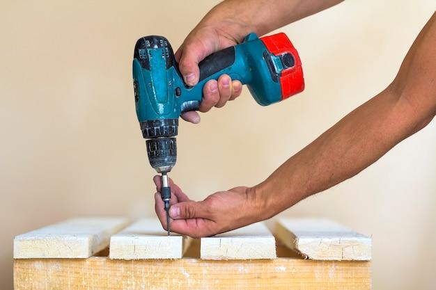 Main d'un ouvrier visse une vis dans une planche de bois avec un tournevis sans fil