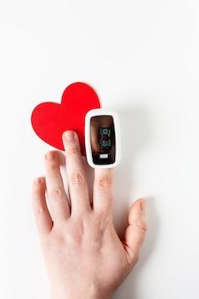 Main avec oxymètre de pouls sur un doigt et un symbole du cœur