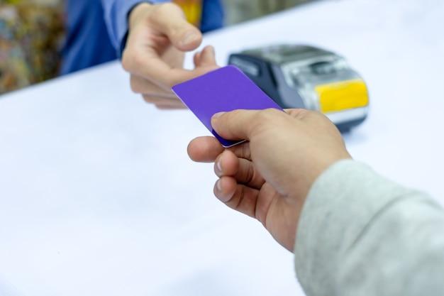 Main de paiement par carte de crédit sur le terminal de paiement avec caissier sur la table