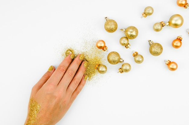 Main avec des paillettes et des boules de décoration