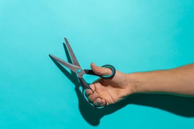 Main avec une paire de ciseaux colorés devant un fond bleu avec espace de copie pour le texte