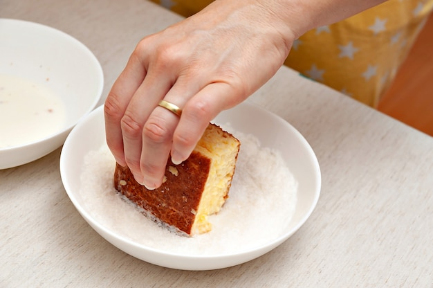 Main passant dans la noix de coco râpée dessert brésilien traditionnel appelé en portugais brésilien: bolo gelado.