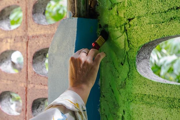 Main de peintre peignant un mur avec un pinceau
