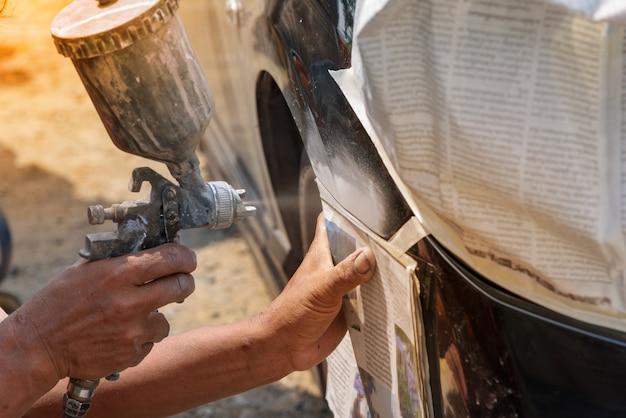 Main de peintre de réparateur d'automobile avec le pulvérisateur d'aérographe