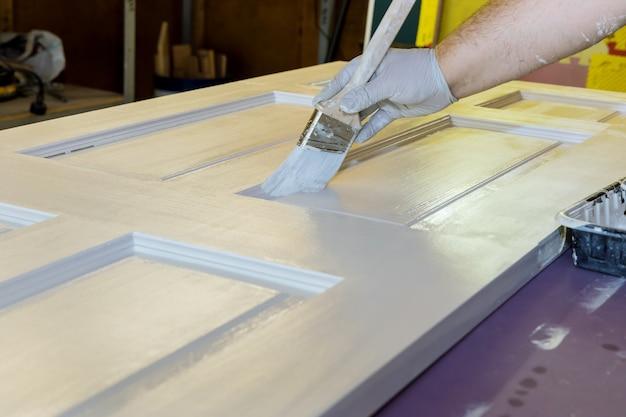 Main de peintre réparateur avec des gants avec des peintures porte d'entrée en bois à l'aide d'un pinceau dans une nouvelle maison
