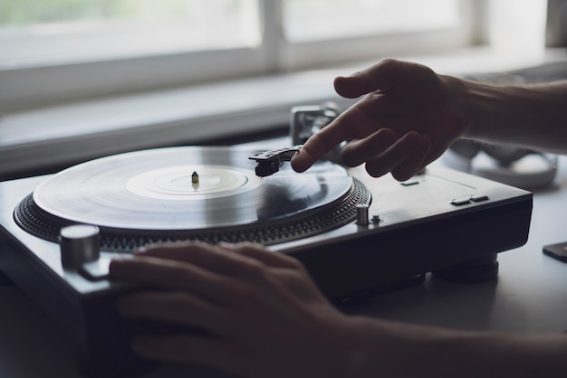 La main d'une personne en gros plan a mis l'aiguille sur un disque, jouant un disque vinyle à la fête