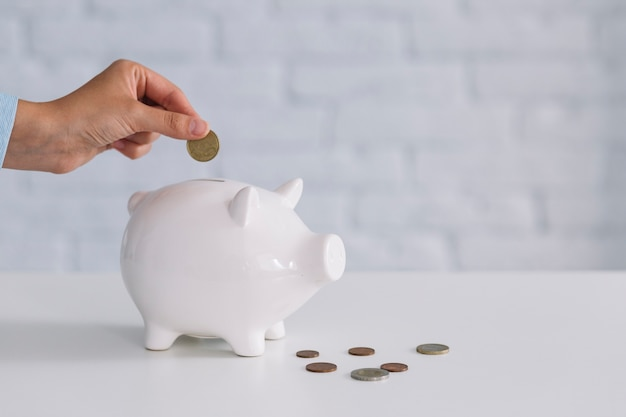 Main d'une personne insérant une pièce de monnaie dans une tirelire blanche sur un bureau