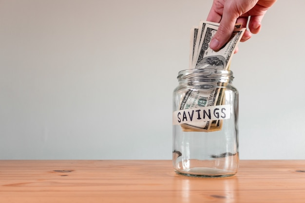 Main d'une personne mettant des factures en dollars américains dans un bocal en verre étiqueté «économies»