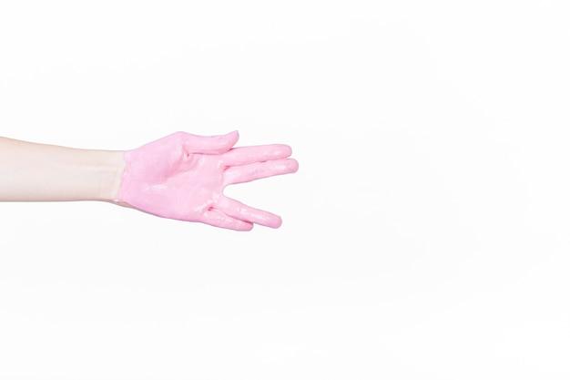 Main d'une personne avec de la peinture rose faisant salutation de vulcan