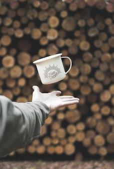 La main de la personne retournant une tasse blanche avec un imprimé happy camper