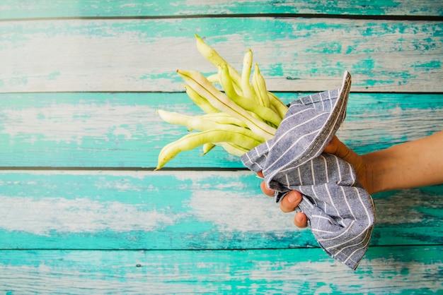Main de la personne tenant des haricots frais enveloppés dans une serviette sur fond en bois