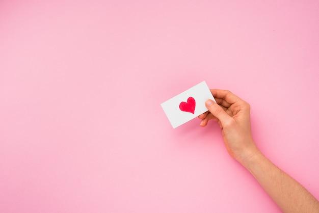 Main personne tenant papier avec image de coeur