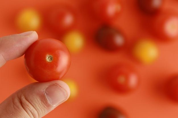 La main de la personne tenant une tomate cerise sur un arrière-plan flou