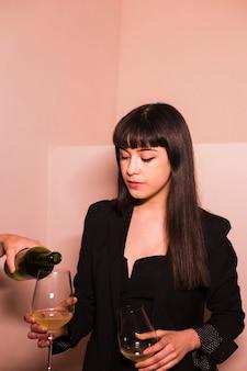 Main de la personne verser le vin dans le verre à une femme