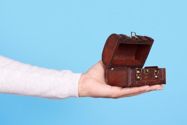 Main avec petit coffre en bois isolé
