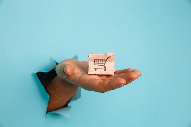 La main avec une petite boîte de livraison à travers un trou de papier bleu.